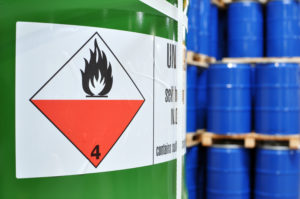 Green chemical container that has label with warning flame.